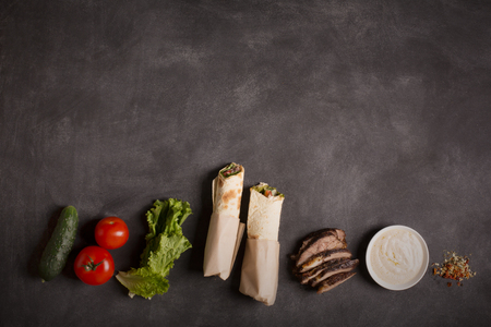 tzaziki: Doner kebab - fried beef meat with vegetables in tortilla on the black chalkboard. Copy space Stock Photo