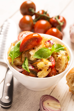 Italian Appetizer salad with tomatoes, bread,bazil mixed with lemon juice in the white bowl