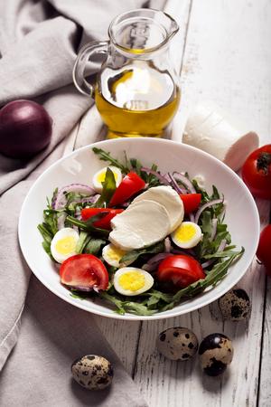 Italian salad prepared with arugula, mozzarella, eggs. white wooden background Stock Photo