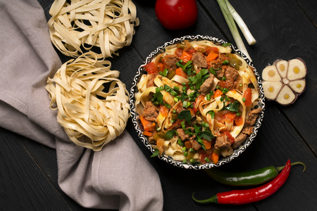Traditional asian noodle lagman with vegetables and meat Stock Photo
