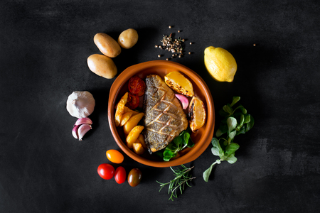 Baked dorado with fresh salad and vegetables on the plate. Stock Photo