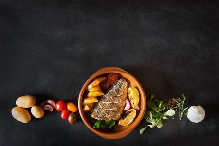 Baked dorado with fresh salad and vegetables. Top view. Ingredients are on the table