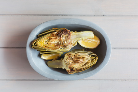 Artichokes and lemons on the plate. White wooden background. This product has one of the highest antioxidant capacities