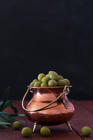 Fresh green olives in the metallic jar on the black background