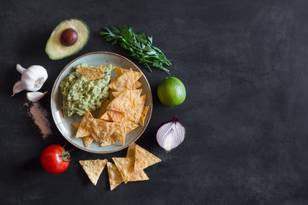 Plate of guacamole with tortilla chips and ingredients with copy space Stock Photo