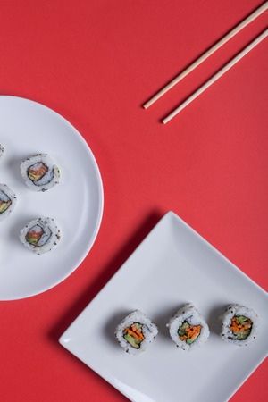 Japanese sushi on a red background. Rolls and sticks for traditional asian food. Top view