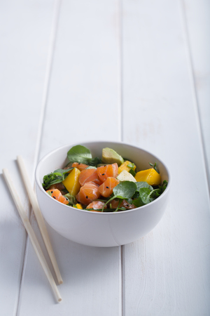 Hawaiian Poke salad with salmon, avocado and vegetables in a bowl on a white wooden rustic background with copy space above