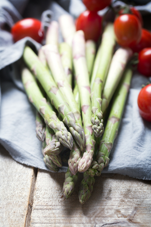 Bunches of fresh green asparagus and tomatoes on wooden background. Rustic style, vertical orientation