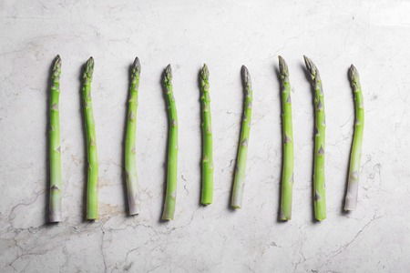 Fresh green asparagus on stone marble background. Horizontal orientation