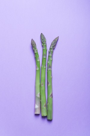 Banches of fresh green asparagus on purple background. Vertical orientation Stock Photo
