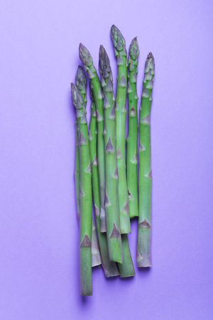 Bunches of fresh green asparagus on purple background. Vertical Stock Photo