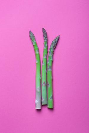Three fresh green stem of asparagus on purple background. Vertical orientation