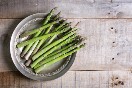 Bunches of fresh green asparagus on wooden background. Rustic style with copy space Banco de Imagens