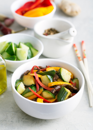Traditional Asian stir fry salad contains meat, pepper and vegetables. Seasoned with soy sauce