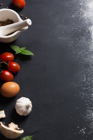 Baking background with copy space on black surface for your text. Flour and vegetables are traditional ingredients for breadmaking and other baking. Often used in mediterranean cuisine Standard-Bild