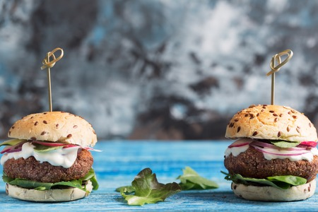 Veggie falafel burgers with fresh vegetables on blue background with copy space Stock Photo