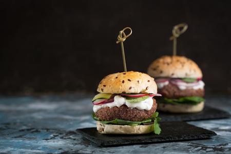 Veggie falafel burgers with fresh vegetables on dark background Stock Photo