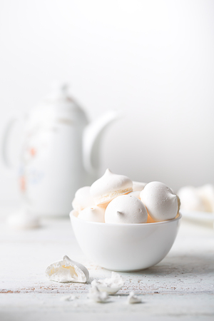 Meringues sweet dessert and teapot on white wooden table