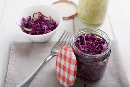 Homemade fermented cabbage in jars on a wooden table