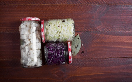 Sauerkraut in a blue bowl on a wooden table. Top view