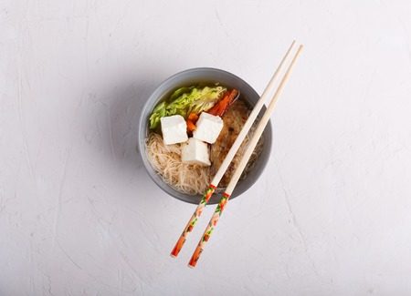 Traditional spicy asian soup with tofu cheese and noodles.
