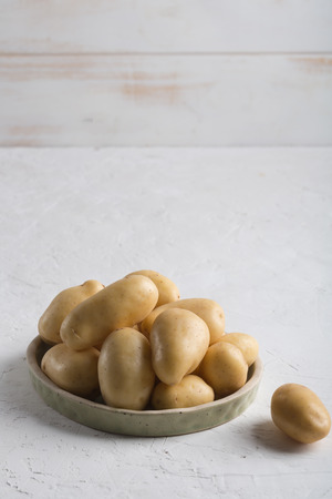 Pile of raw potatoes in the bowl on white background