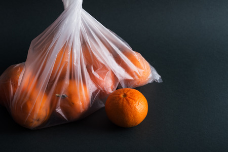Oranges in plastic bag on a black
