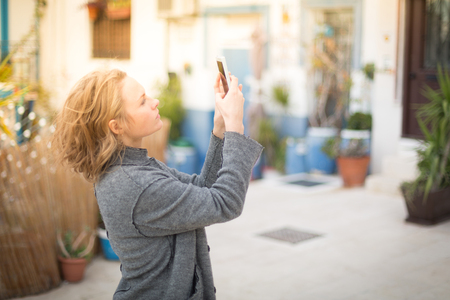 Stylish young woman in a gray coat outside the home make photos of the town