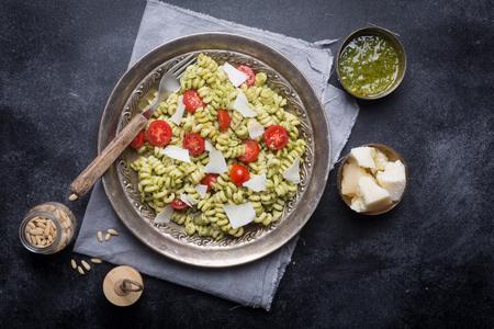 Plate of pasta fusilli with pesto sauce and cherry tomatoes on dark Фото со стока