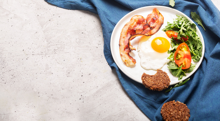 Photo of hearty high protein english style breakfast with egg, fried bacon and arugula on the plate
