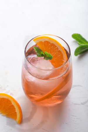 Fresh ice tea summer cocktail with orange and ice in glass on white Reklamní fotografie