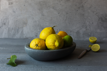 Still life with fresh yellow lemons in a bowl