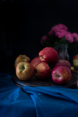 Still life with apples and flowers on a metallic plate. Dark style photo Stock Photo