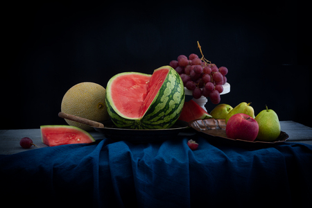 Still life with fresh watermelon and fruits on the table. Dark retro style photo. Black background