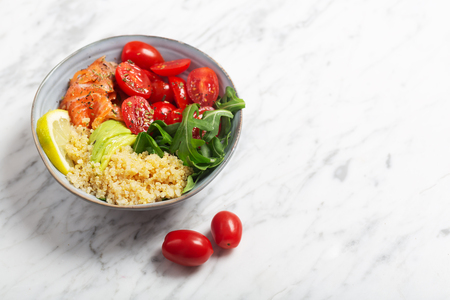 Dietary bowl salad with quinoa, salmon and vegetables, such as tomatoes and arugula. Fresh vitamin organic salad.
