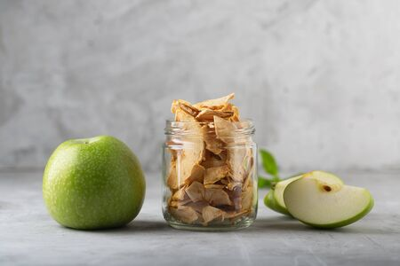 Apple chips in a jar l and pieces of this fruits on a table. Horizontal orientation