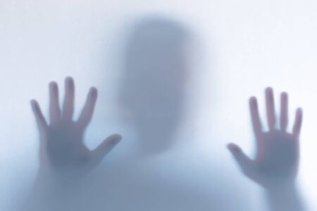 Blurred scary ghost silhouette behind a white glass background. Horizontal orientation