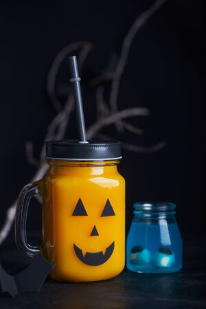 Halloween healthy pumpkin or carrot drinks in the glass jar, artificial eyeballs in a blue liquid on a black background
