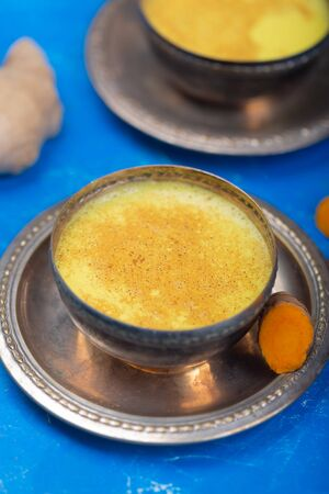 Golden turmeric milk on the blue  with ingredients