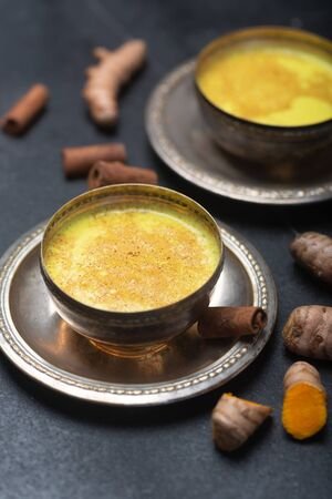 Golden turmeric milk on the black  with ingredients
