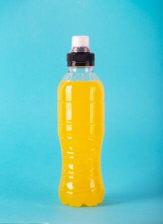 Bebida energética isotónica. Botella con líquido amarillo transparente, bebida deportiva en un colorido
