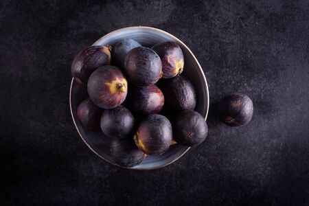 Fresh figs in a bowl on a dark wood background, top view with copy space