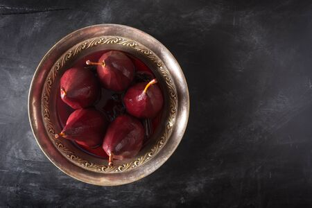 Poached Pears in red Mulled Wine With Cinnamon and Anise Stockfoto - 129800431