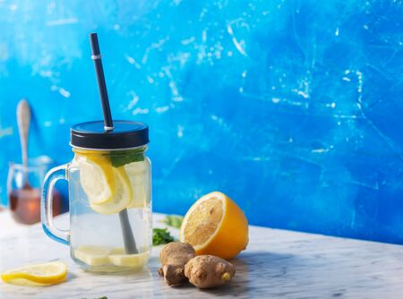 Ginger Water in Glass jar With Lemon and Honey on Blue Background With Copy Space Stockfoto
