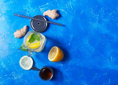 Ginger Water or tea in Glass jar With Lemon and Honey. This Drink is a Natural Anti-Inflammatory Agent That Acts as an Antioxidant and Improves Blood Sugar. Blue background, Flat lay Stockfoto