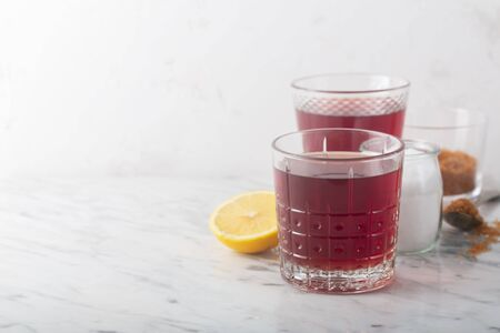 Homemade Isotonic Energy Drink and Ingredients. Glass With Red Liquid, Natural Sport Beverage on a Stone Background. It Usually Contains Salt and Sugar and Maintains Optimal Hydration by Replacing Vital Minerals and Eelectrolytes