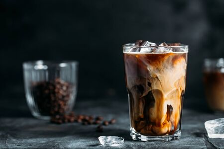 Ice coffee in a tall glass with cream poured over and coffee beans on dark gray