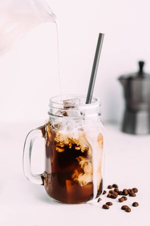 Pouring milk into glass with cold coffee drink in glass jar and coffee beans.