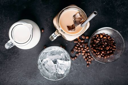 Cold brewed iced coffee in glass and coffee beans, glass jar with milk, ice cubes on dark