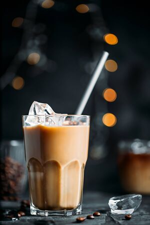 Ice coffee in a tall glass with metal straw and coffee beans on dark